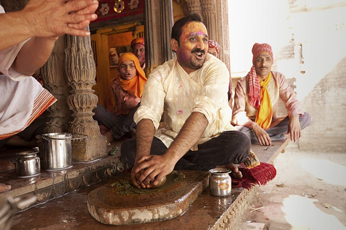 A man grinds the ingredients for preparing bhang using a mortar and pestle.