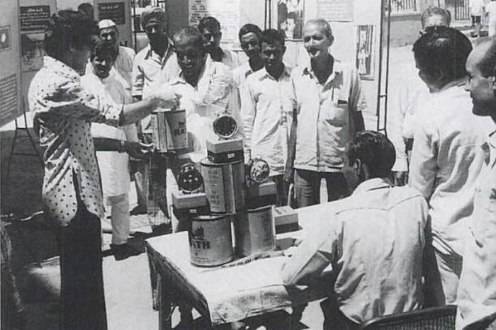 Sterilised men are given ghee and clocks as rewards for undergoing vasectomy. At Dujana House 6 Sept, 1976. Image & Caption Source: PD-PIB-New-Delhi / Unsettling Memories: Narratives of the Emergency in Delhi By Emma Tarlo