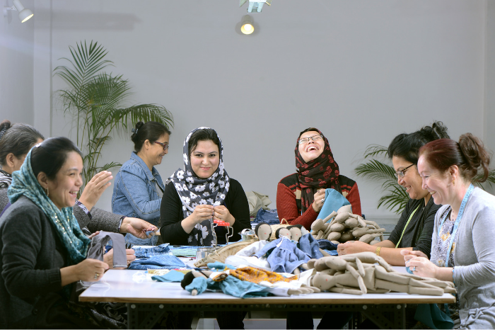 Afghani refugee women working stitching and making Silaiwali dolls working and laughing wearing hijab