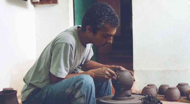 an indian man making pots on a potter wheel during vacation with an artist