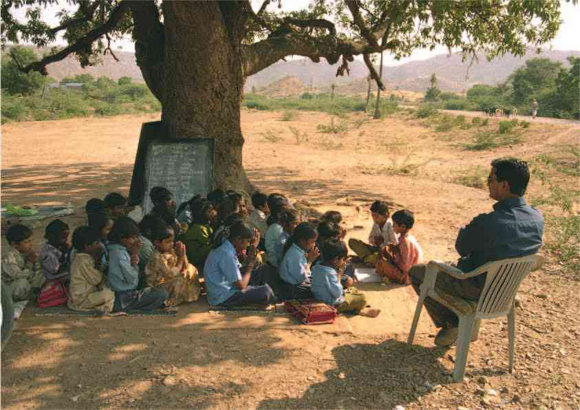 students in rural india learning under a tree