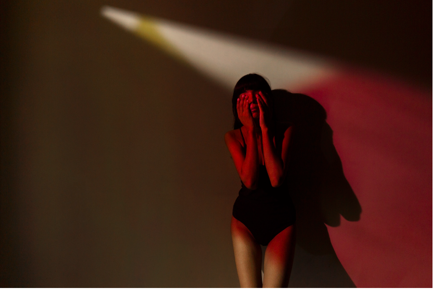 Image of a woman shutting her eyes. Thinking or hiding.