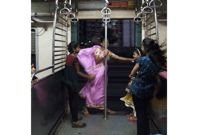 """""""A lady puts her hand out on the door so that the kids with her can't lean outside the ladies compartment of the Mumbai local train."""""""
