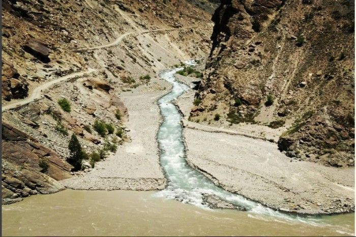 The clear blue stream joins into the muddy Spiti River