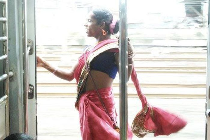 """""""Swidal poses for a picture in the ladies compartment of the Mumbai local train. She told me that she covers herself up like this so that she can protect herself from the heat."""""""