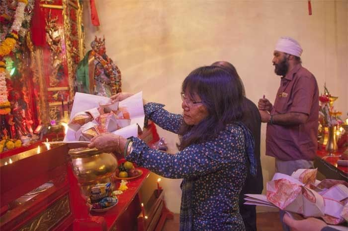 A woman from the Indian Chinese Community performs rituals in the temple while an Indian Sikh guy too prays to the demi god. Photo by: Rashi Arora
