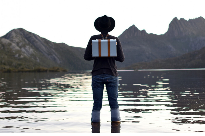 Man with hat standing in water staring at the mountains in front of him wearing Nappa Dori Dean Backpack