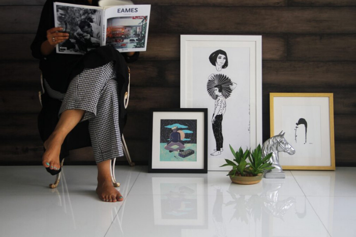 Woman sitting crosslegged reading EAMES magazine with artworks stacked nearby