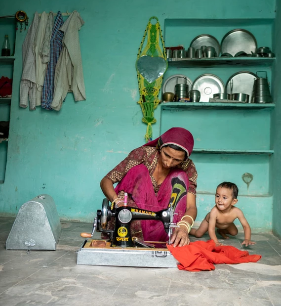 Dhanno on the sewing machine, with her child playing by her side