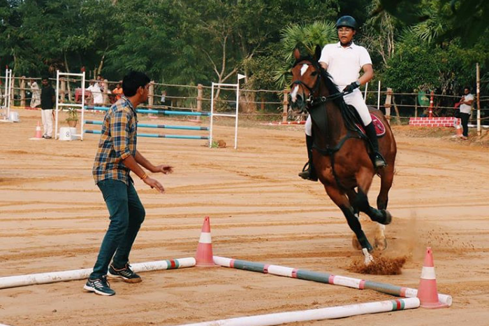 Man on horse while other man watches at Red Earth Riding School Auroville